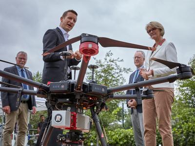 """Cyrill Stachniss, einer der beiden Sprecher des Exzellenzclusters """"PhenoRob"""", erklärt Anja Karliczek, wie der Einsatz von Robotern und Drohnen für die Agrarwirtschaft der Zukunft erforscht wird. (© Foto: Volker Lannert / Uni Bonn)"""