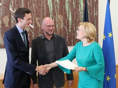 Foto (v.l.): Dr. Alexander Schmithausen und Dr. Manfred Trimborn nehmen aus der Hand von Ministerin Julia Klöckner den Förderbescheid entgegen.